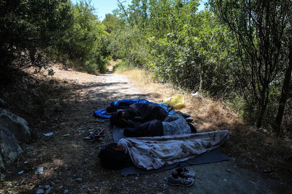 Fotografía de unos migrantes en la frontera entre Italia y Francia durmiendo en el suelo (del lado italiano) esperando a que anochezca para intentar cruzar de nuevo.