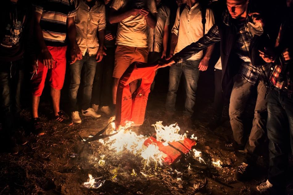 Un grupo de sirios que acaba de llegar por mar a las costas griegas quema sus chalecos salvavidas para llamar la atención de la policía ya que no saben a dónde ir ni qué hacer.