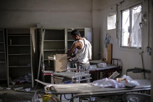 Un trabajador sanitario rescata medicamentos y equipo de la sala de emergencia del hospital de Abs en Hajjah, Yemen, luego del ataque aéreo del 15 de agosto de la coalición liderada por Arabia Saudita que destruyó la estructura y mató a 19 personas