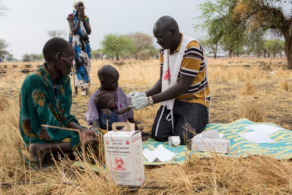 El promotor comunitario de salud, Gatbel, examina a un niño por paludismo en una clínica externa en Thaker, Sudán del Sur. ©Siegfried Modola