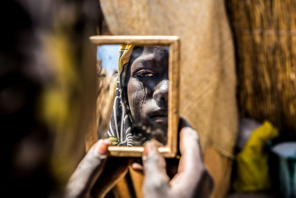 Una mujer que acude a una clínica prenatal de MSF en Diffa, Níger, mira su reflejo en un espejo de mano. ©Juan Carlos Tomasi/MSF