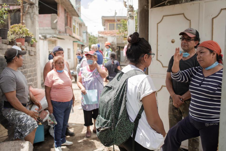 Laura Carmen, de 27 años, habla con un vecino de San Gregorio, cuya casa ha quedado inhabitable tras ser severamente dañada por el terremoto. ©Jordi Ruiz Cirera