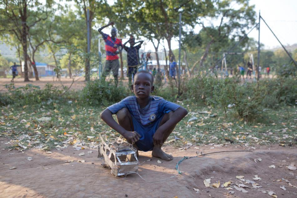 Un niño muestra su camión de juguete hecho con latas de aceite de cocina en el campo de refugiados de Kule, en Gambella (Etiopía).