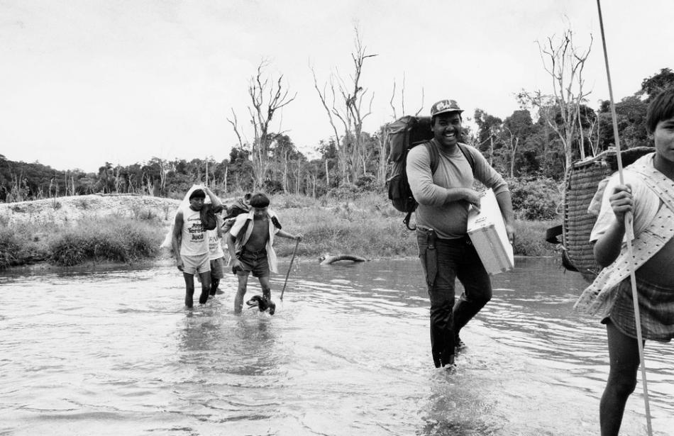 Varios locales nos ayudan a cargar con el material a través del río.
