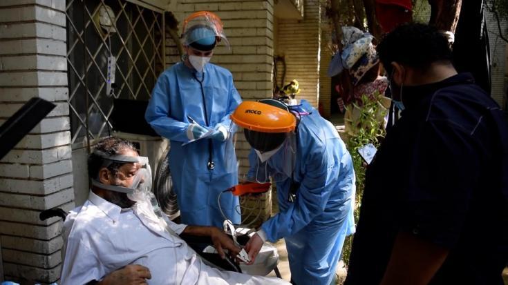 Médicos de MSF examinan a un paciente con COVID-19 en la unidad de cuidados respiratorios del hospital al Kindi en Bagdad.