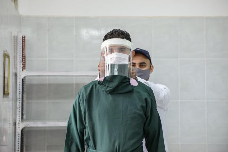 Uno de nuestros trabajadores le ajusta el equipo de protección contra el COVID-19 a otro en Al-Sahul, Yemen. Julio de 2020