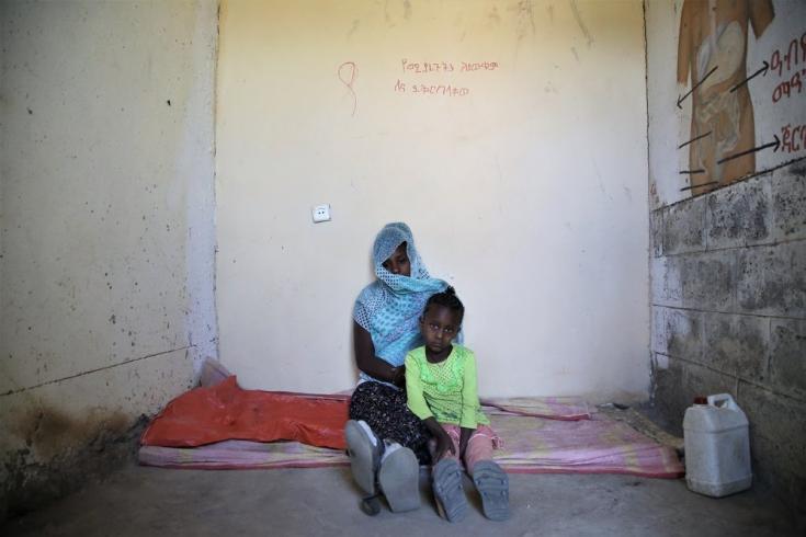Leterbrhan y su hija de 5 años en la pequeña habitación de la escuela primaria Abi Adi en la que duerme con otras casi 20 personas. Marzo de 2021.