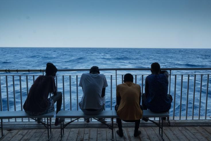 Algunas de las personas rescatadas se reúnen en la popa del Geo Barents y miran el Mar Mediterráneo, dos días después de su rescate. Agosto de 2021