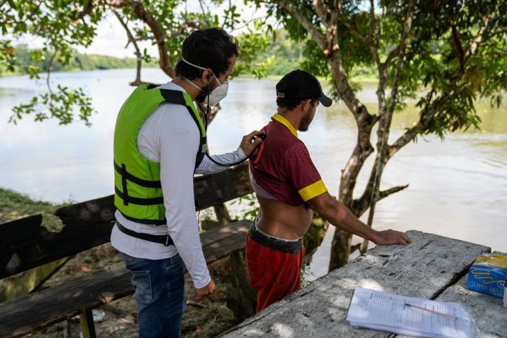 Eduardo Rugani, médico de MSF, examina a un paciente al lado del río Anapu. Brasil, julio de 2021