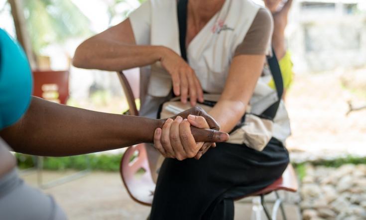 Nadine toma la mano de nuestro personal mientras le curan los pies. Días antes, ella y su hija tuvieron que detener su marcha en medio del Darién porque tenían sus pies en carne viva. Su compañero las dejó allí y 3 días después volvió.