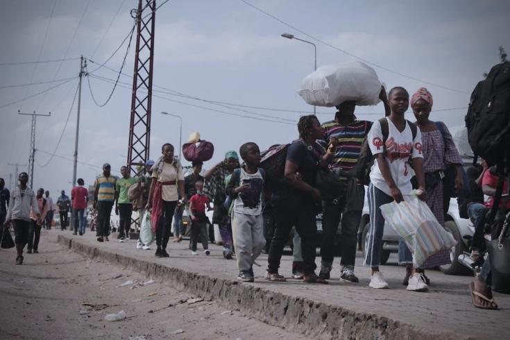 Tras la erupción del volcán Monte Nyiragongo, las personas huyen de Goma llevando sus pertenencias. República Democrática del Congo, mayo de 2021