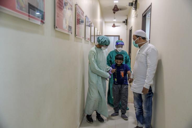 Nuestros enfermeros acompañan a un niño de 9 años con tuberculosis a la sala de electrocardiogramas, en nuestra clínica independiente en Mumai. India, marzo de 2021