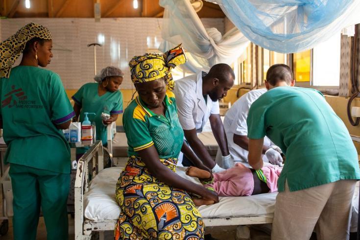 La madre de Warda Kaladjavai lo sostiene mientras los médicos le cambian las vendas. Warda tuvo un accidente de motocicleta en Maroua y ella lo llevó directamente al hospital.