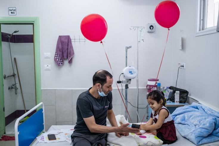 Hala ríe mientras habla por videollamada con su madre y sus hermanas, un día después de que los cirujanos de nuestra unidad de reconstrucción de extremidades del hospital Al-Awda le operaran el pie. Gaza, agosto de 2021