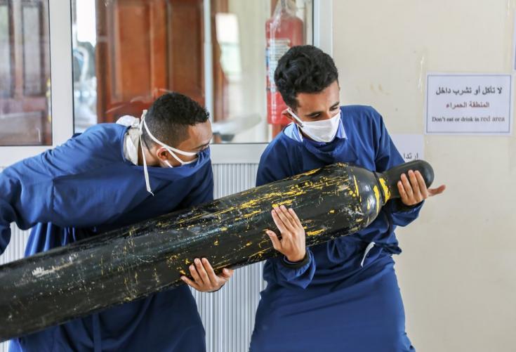 Dos trabajadores del centro Al-Sahul de COVID-19 están tratando de trasladar una botella de oxígeno al interior de la Unidad de Cuidados Intensivos. Yemen, julio de 2020