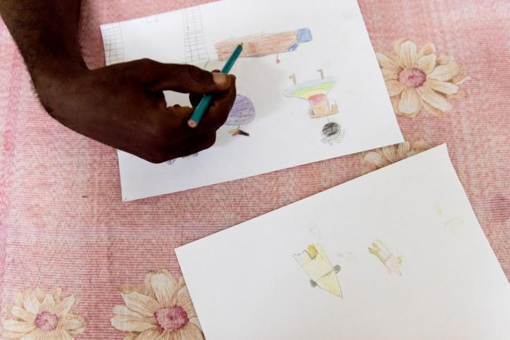 Aimé-Césaire Likosso, asesor de salud mental, señala detalles en algunos dibujos hechos por niños y niñas sobrevivientes de violencia sexual. República Centroafricana, noviembre de 2020.