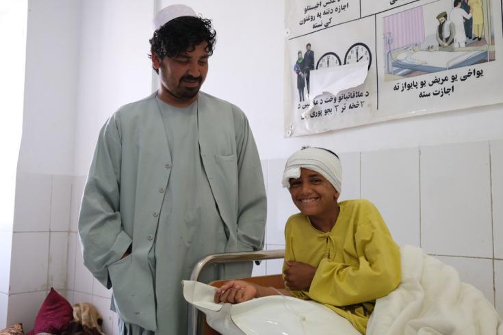 Samiullah, de 12 años, sonríe junto a su tío Ahmadullah en el hospital de Boost, tras haber recibido atención por una herida de bala que recibió en la cabeza el 4 de mayo. Afganistán, mayo de 2021
