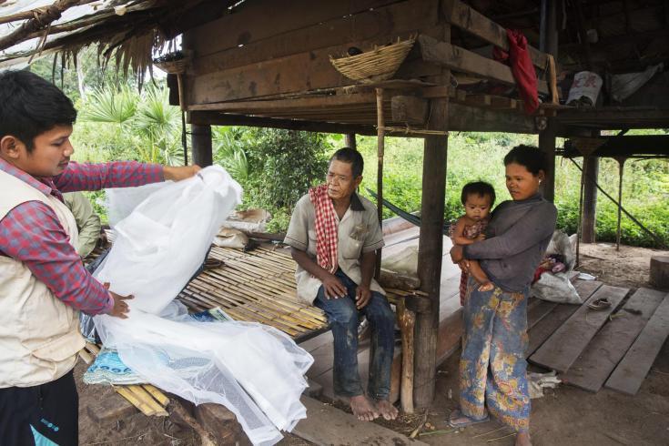 Un enfermero de MSF reemplaza las mosquiteras de la familia de a Saom Koem, quien recibió tratamiento para la malaria dos años atrás en Camboya (2016).