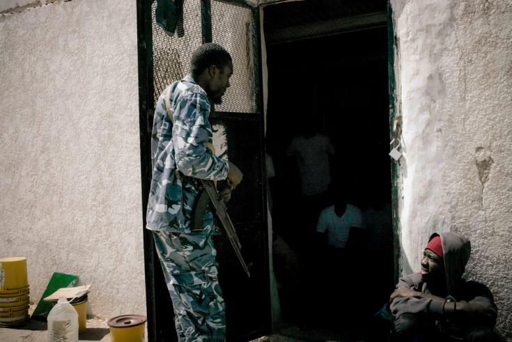 Guardia armado escolta detenidos en el centro de detencion Abu Salim, en Trípoli, Libia.