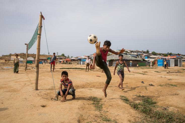 Niños jugando al fútbol en un terreno donde los refugios fueron retirados, ya que se encontraban en una zona de riesgo de monzón, en el campo de refugiados de Kutupalong, en Bangladesh.