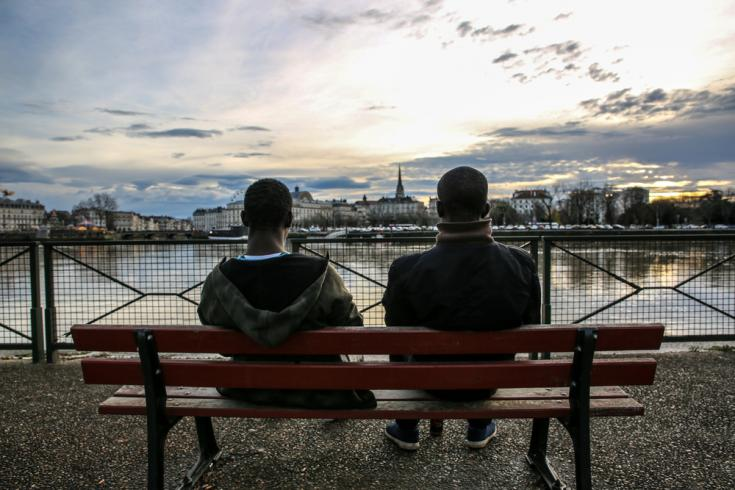 Dos migrantes descansan frente al río Adour en Bayona, justo al otro lado de la frontera con España.
