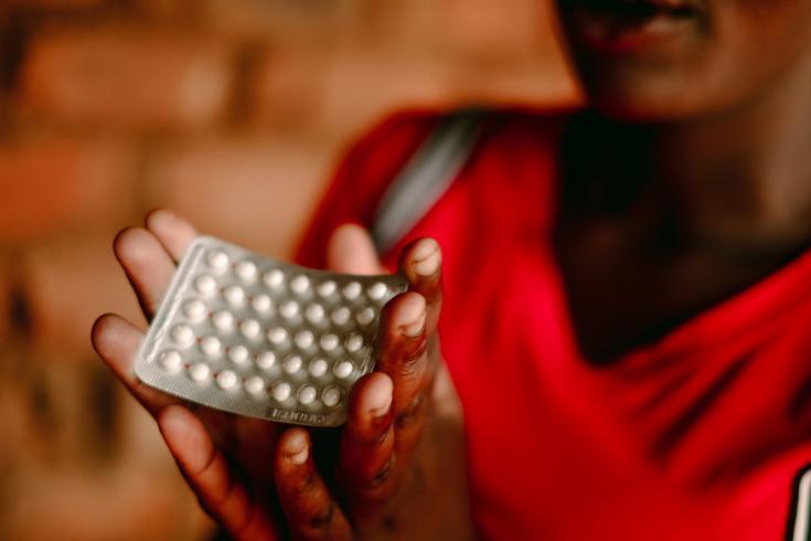 Foto tomada en Malaui, 2019. Una trabajadora sexual sostiene anticonceptivos durante una sesión de promoción de la salud.