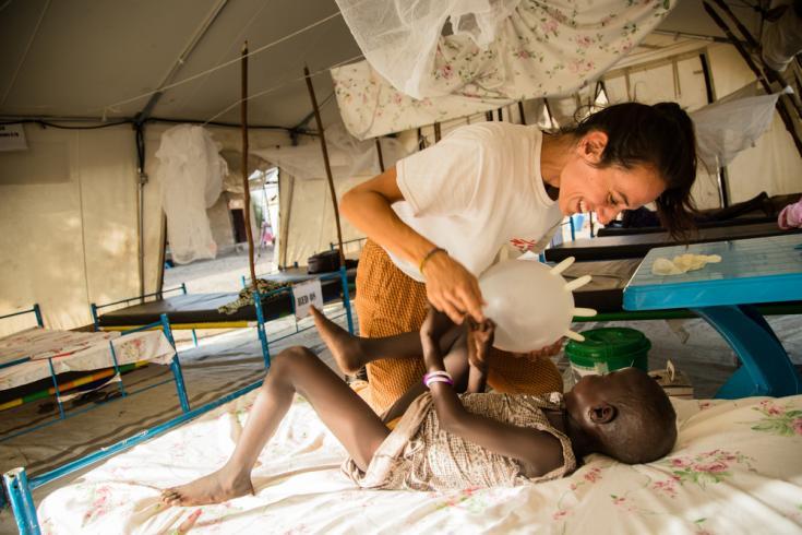 Nuestra enfermera Bárbara García y el pequeño Nyamach juegan con un globo hecho con un guante quirúrgico, en la sala de pacientes hospitalizados de nuestro hospital en Ulang, en el noreste del país.