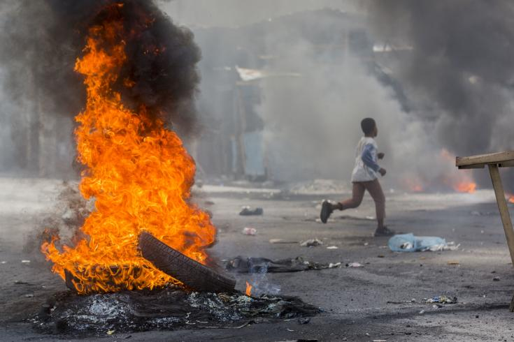 Un niño atraviesa una barricada durante las protestas de 2019 en Puerto Príncipe, Haití.