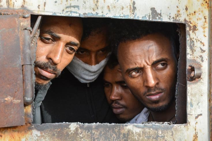 Varios refugiados detenidos miran a través de un hueco de una puerta, en el centro de detención de Zintan.