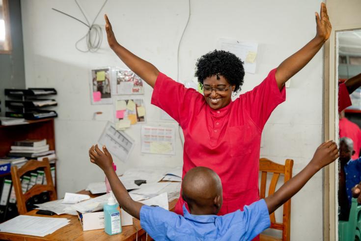 """Un fisioterapeuta de MSF en el centro de traumatología de MSF """"L'Arche de Kigobe"""" le da ejercicios de rehabilitación a un paciente joven a quien le quitaron el yeso del brazo."""
