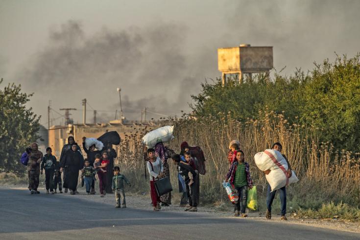 Civiles sirios, tanto árabes como kurdos, huyen con sus pertenencias debido a los bombardeos turcos en la ciudad de Ras al Ain, en la provincia de Hasakeh, a lo largo de la frontera turca, el 9 de octubre de 2019.