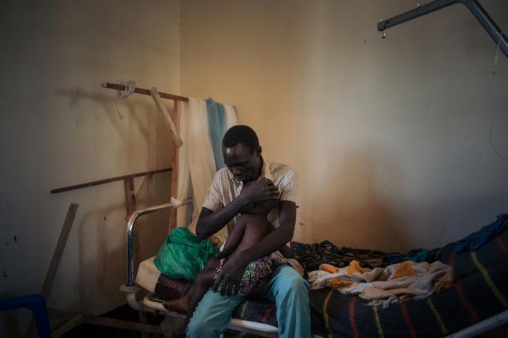 Joseph Drobho Giria sostiene a su hija de 2 años, Bhileru Drobho, en la unidad que dirigimos en el Hospital Biringi, en la provincia de Ituri. La pequeña tiene sarampión.