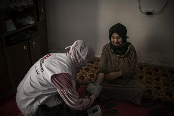 Hala, enfermera, midiendo la presión arterial de Maryam durante una visita a domicilio. Maryam es una mujer siria de 90 años sufre ceguera pero también diabetes e hipertensión. Burj al-Barajneh, Beirut, Líbano.