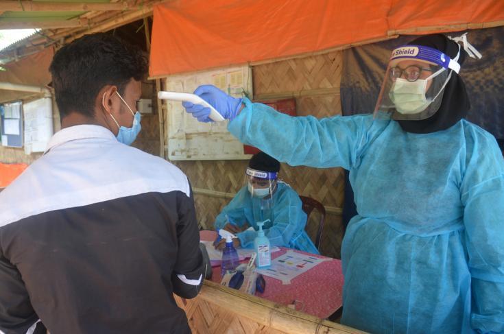 El personal de MSF examina a los pacientes para detectar síntomas respiratorios y fiebre en la entrada del hospital Goyalmara para madres e hijos en Cox's Bazar, Bangladesh.