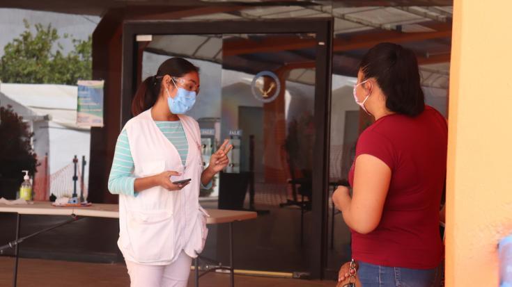 Promotora de salud de MSF recibe y guía a una familia a su visita en el centro COVID-19 en Matamoros, México.