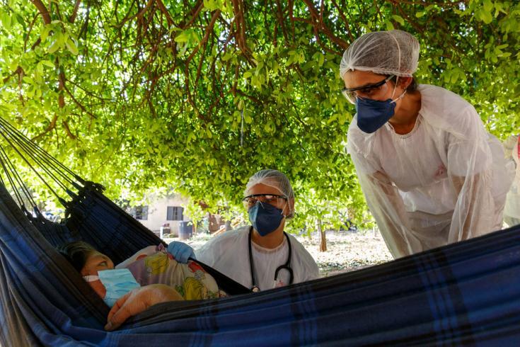 La Dra. Luiza Cegalla y la enfermera Erica Cravo junto a una paciente con COVID-19 en su casa de la aldea de Limão Verde, Brasil.