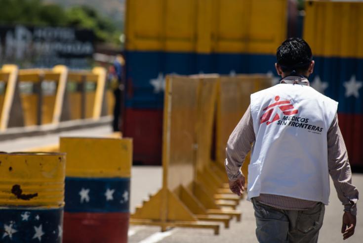 Un miembro del equipo de Médicos Sin Fronteras (MSF) cruza el Puente Simón Bolívar que conecta a Colombia con Venezuela. Cientos de venezolanos retornados cruzan el puente todos los días a pie para regresar a su país debido a la pandemia COVID-19.