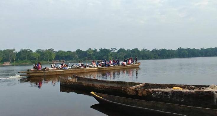Un equipo de vacunación y sus bicicletas son transportadas río abajo en un bote de piragua.