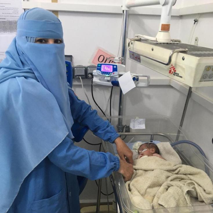 Enfermera de Médicos Sin Fronteras junto a un pequeño paciente en Yemen.