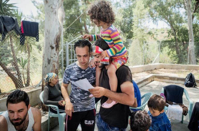 Refugiados sirios leen el permiso dado por la policía que les permite quedarse 6 meses en Grecia © Alessandro Penso
