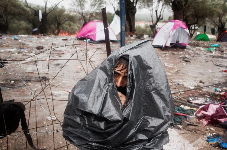 Un refugiado afgano se protege con una bolsa de basura durante una tormenta en el centro de recepción de Moria (Grecia) mientras espera sus documentos. ©Alessandro Penso