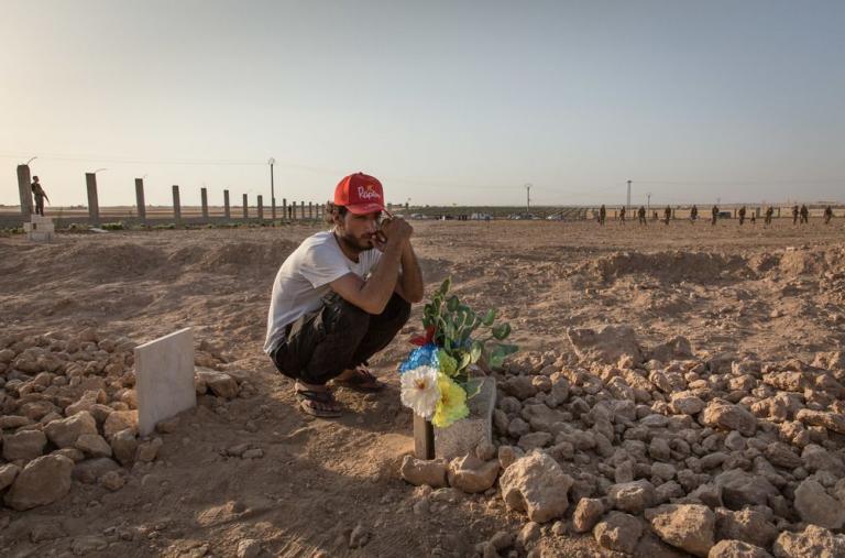 Tal Abyad, Siria - Ismael se sienta en la tumba de su primo y amigo, Hout, quien fue asesinado dos días antes durante la batalla por Raqqa, Siria. ©Chris Huby