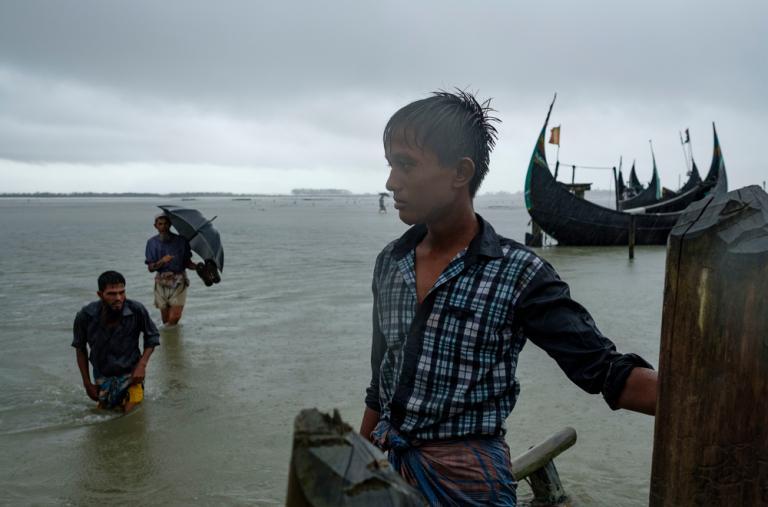 Un niño de Bangladesh observa a los refugiados rohingya que llegan bajo una lluvia torrencial en un paso fronterizo en el río Naf, cerca de Teknaf, tras escapar de Myanmar. Casi 650.000 rohingyas han huido a Bangladesh desde Myanmar. ©Antonio Faccilongo