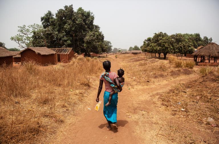 Christina y su hija Veronique, que sufría de malaria, regresan a su casa después de visitar el centro de vacunación en la aldea de Ndongue, República Centroafricana.