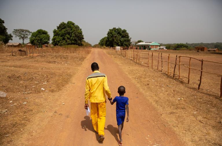 Leonard y su hijo Euphreme (6) abandonan el lugar de la vacunación hacia su casa. Acompañado por su padre, el pequeño estaba muy enfermo cuando lo llevaron al puesto de vacunación.
