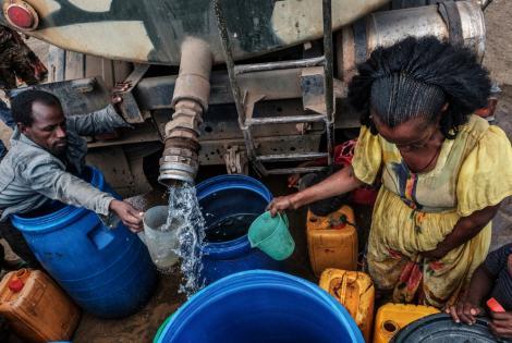 Un hombre y una mujer recolectan agua distribuida por las Fuerzas de Defensa de Etiopía (EDF) en la aldea de Hadaelga, cerca de Chercher, en Etiopía. 8/12/2020.