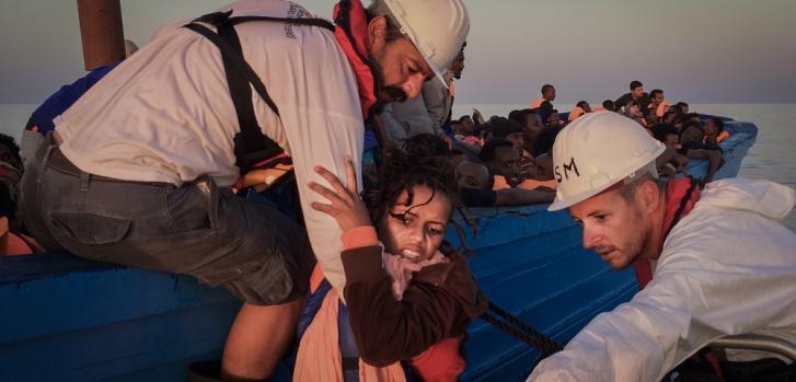 Una mujer es rescatada de un pequeño bote de madera a la lancha que la llevará al barco de Médicos Sin Fronteras ©Nicolás Castellano/SER