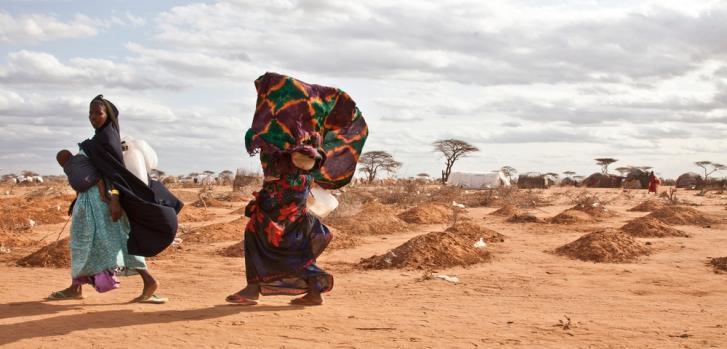 Refugiadas somalíes pasan a través de tumbas en el campo de refugiados de Dadaab