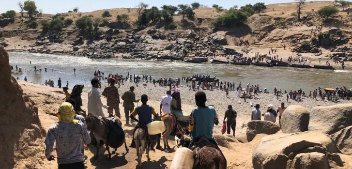 El paso fronterizo de Hamadayet, donde refugiados de Etiopía cruzan el río hacia Sudán. Los recién llegados se llevan todas las pertenencias que pueden llevar consigo, algunos se quedan con el ganado y otros sin nada.