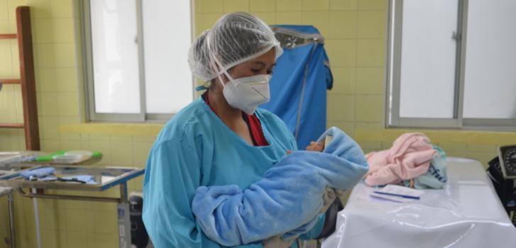 Una de nuestras enfermeras lleva en brazos un bebé recién nacido, para su primer control de peso y talla, en el Centro de Salud San Roque, de la ciudad de El Alto. Bolivia, abril de 2021